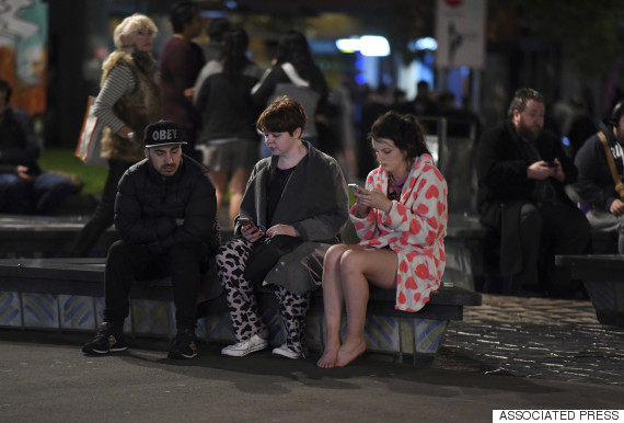 People evacuated from buildings along Dixon Street check their mobile phones while sitting on a bench in Wellington after a 6.6 earthquake based around Cheviot in the South island shock the capital, New Zealand, Monday, Nov. 14, 2016. A powerful earthquake struck New Zealand near the city of Christchurch early Monday, with strong jolts causing some damage to buildings over 200 kilometers (120 miles) away in the capital, Wellington. (Ross Setford/SNPA via AP)